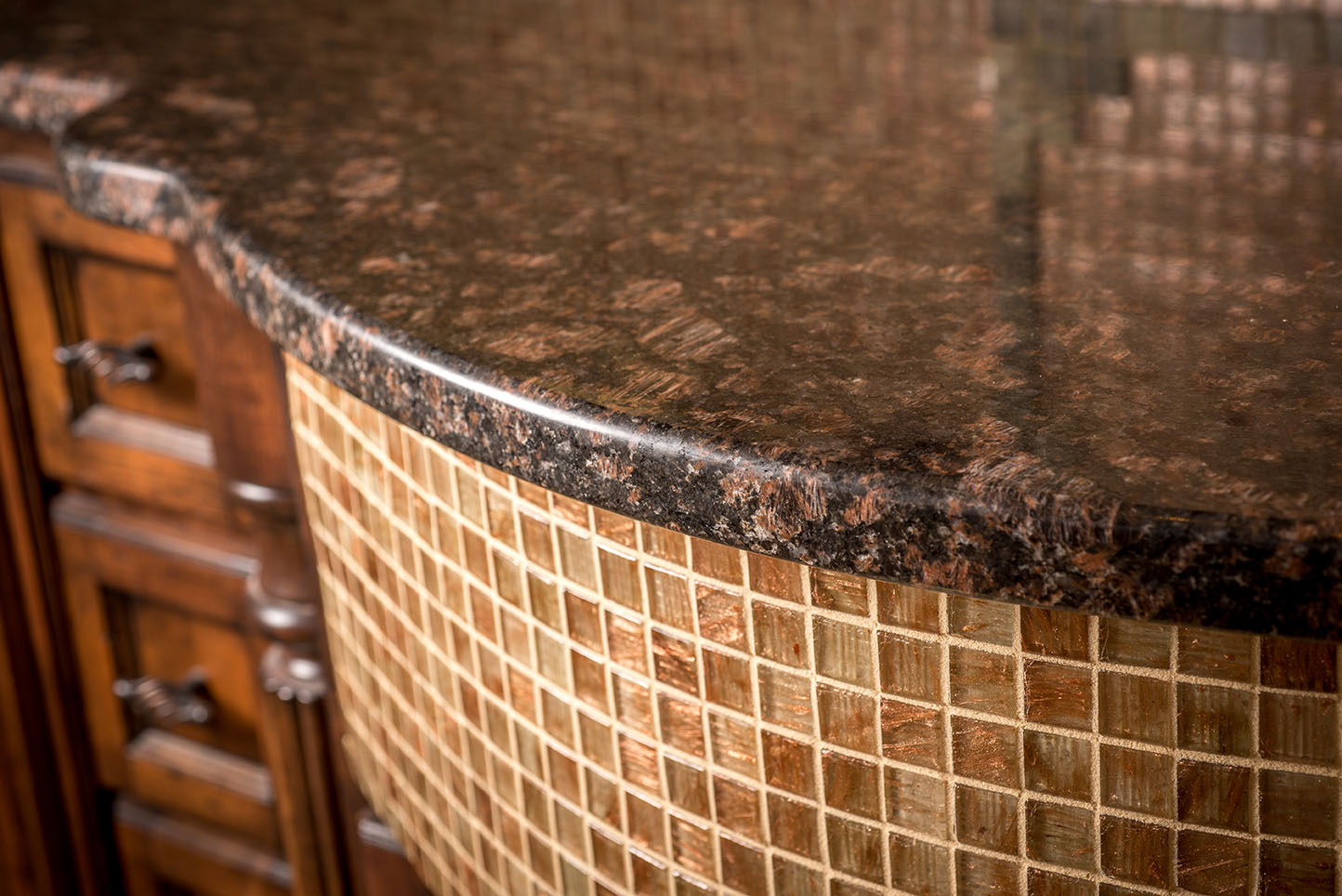 A classy granite kitchen counter with tile cabinet face.  This makes a great transition from the natural stone to your cabinets
