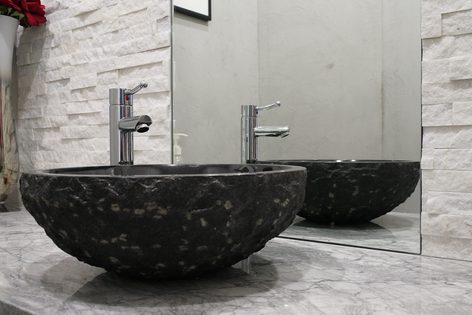 A raw stone vessel atop Super White marble vanity